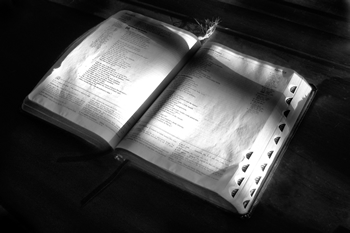 Open Bible with shadow of a cross on the pages